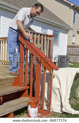 Contract painter staining deck on home