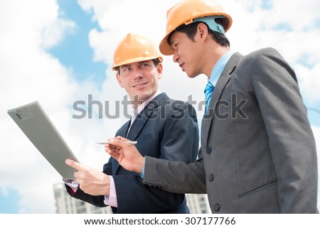 Contractor and investor discussing business document at the outdoor meeting - stock photo