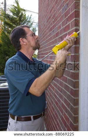 Contractor caulking exterior walls between  frame and brick, sealing to stop possible air leaks, conserving energy - stock photo