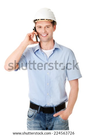 Contractor in hardhat smiles as he talks on his cell phone. - stock photo