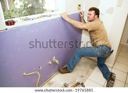 Contractor installing a large piece of drywall during a kitchen remodel. - stock photo
