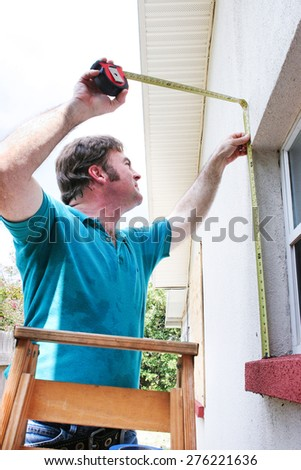 Contractor measuring windows for hurrican shutters to replace plywood.   - stock photo