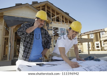 Contractor on call with colleague working on blueprint at construction site