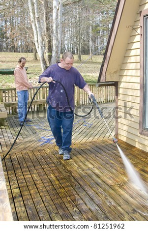 Contractor pressure washing deck that raps around house, getting home ready to sell