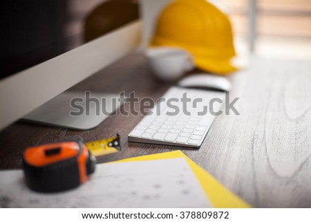 Contractor's desk with a computer and some building plans with a lot of bokeh - stock photo