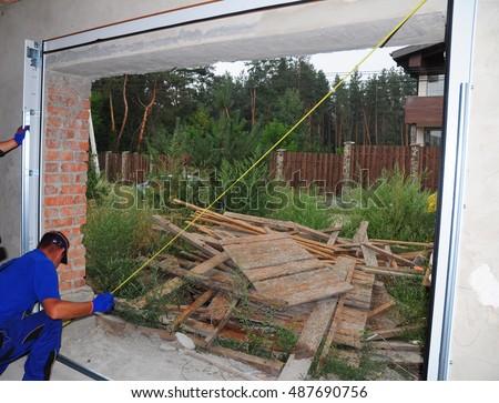contractors installing garage door u0026 garage door opener with measuring tape how to install a