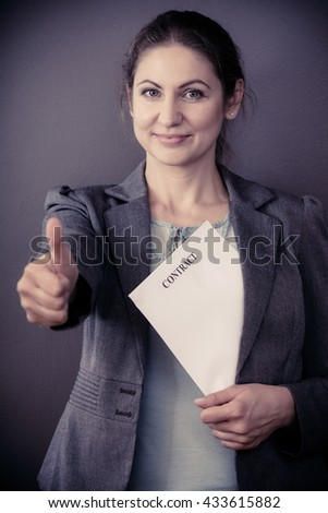 Contracts and agreements concept. Adult beauty woman in jacket holding contract. Close up portrait of person with agreement. - stock photo