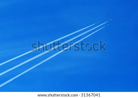 Contrail arrow. Three military jet planes with contrail in the clear blue sky - stock photo