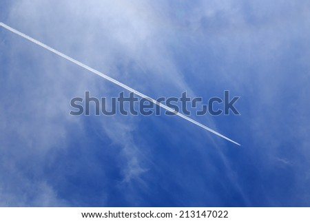 contrails of aircraft against a blue sky. routes in airways - stock photo