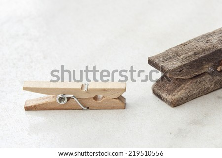 Contrast between small new and big old tweezer clothespin isolated on a textured bright background. - stock photo