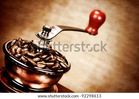 Contrast image of vintage  coffee  mill or grinder with coffee beans .Dramatic lightning - stock photo