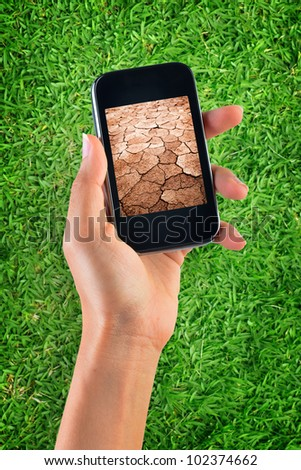 Contrast of green grass and dry soil - stock photo