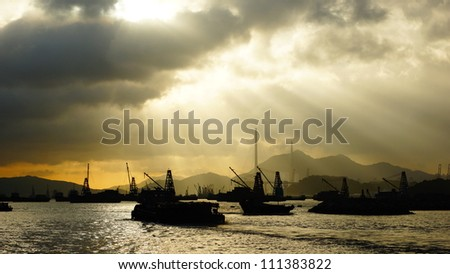 Contre jour in the harbor with the crepuscular rays in hong kong