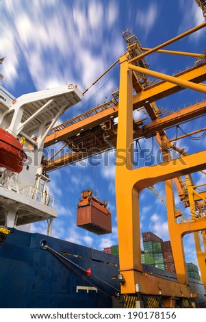 Control cabin in quay crane loading container from containership to container truck on pier - stock photo