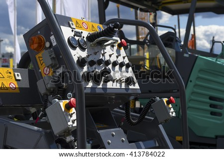 Control panel of asphalt paving machine, heavy industry, dashboard unit with buttons, levers, toggle switches, knobs, signal lights, sensors and indicators, road construction machines on background  - stock photo
