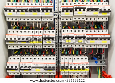 Control panel with many circuit breakers in fusebox - stock photo