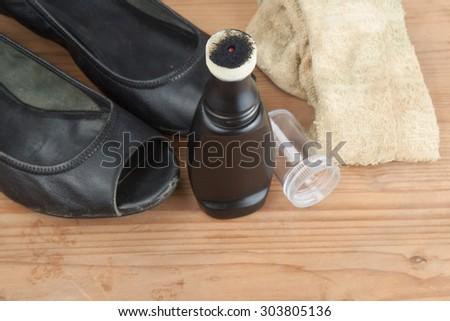 Convenient liquid shoe polish with worn out shoes on wooden platform. - stock photo