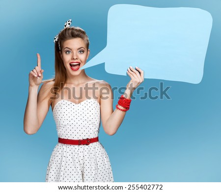 Conversable beautiful woman showing sign speech bubble banner looking happy excited / young American pin-up girl on blue background having idea  - stock photo