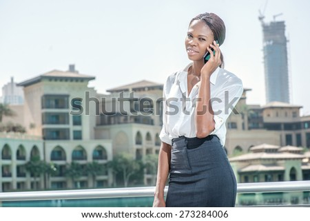 Conversation with the client. African businesswoman businessman holding a cell phone in hand and talking on the phone with a client while standing near the lake in Dubai downtown