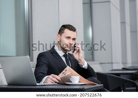 Conversation with the client on a cell phone.Successful and confident businessman sitting at the table drinking coffee and reading a financial newspaper.Young man in formal clothes working on a laptop - stock photo