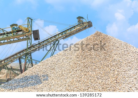 Conveyor and pile of quarry stone for lime industry - stock photo