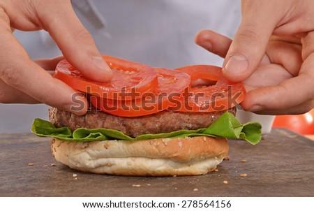 Cook adding tomato on hamburger.Preparing and making hamburger. - stock photo