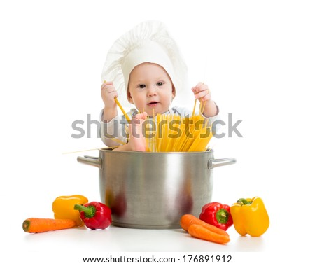 cook baby sitting inside pan with pasta and healthy food - stock photo