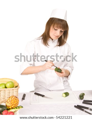 Cook girl cuts the cucumber - isolated on white