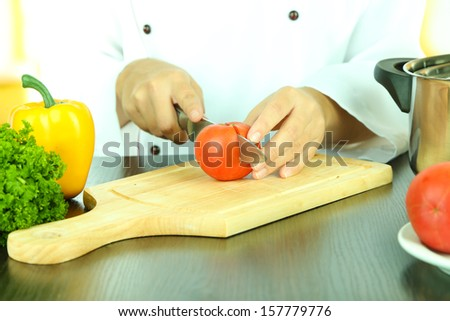 Cook hands cutting tomato