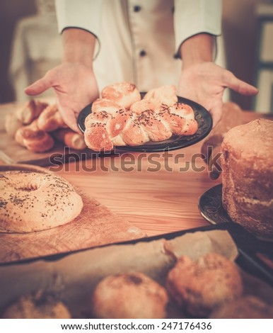 Cook hands holding homemade baked goods - stock photo