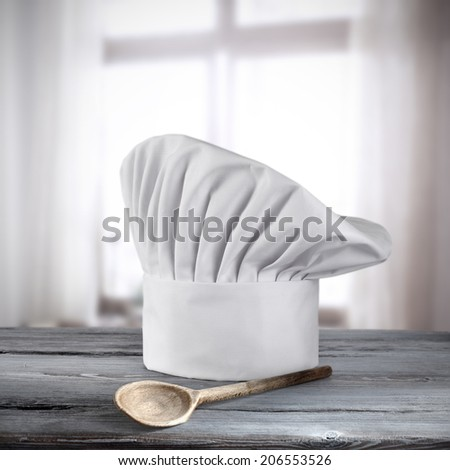 cook hat of white color wooden spoon of brown and window