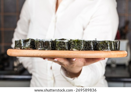 cook holds in hands plate with rolls - stock photo