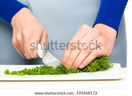 Cook is chopping green dill, closeup shoot, isolated over white - stock photo