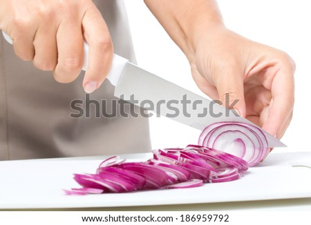 Cook is chopping onion, closeup shoot, isolated over white - stock photo