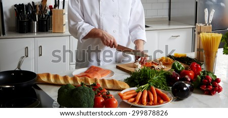 Cook is near the table, cut vegetables to fry them in a skillet and add to the Spaghetti and salmon bake in the oven - stock photo