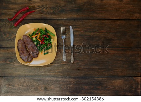 Cook Italian restaurant two steaks cooked pork tenderloin with vegetables. On the table served dinner of tender lamb, served with meat vegetable ragout - stock photo