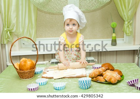 Cook - little girl on kitchen kneads dough, roll a rolling pin and bakes muffins and cakes, fun and hooligans - stock photo