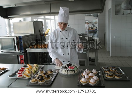 Cook on kitchen prepares meal - stock photo