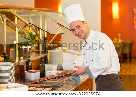 Cook or chef filling a buffet at restaurant with cold meat - stock photo