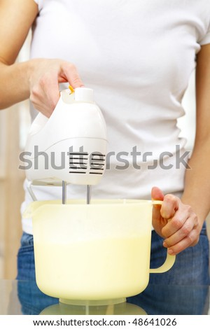 cook preparing cream using a kitchen mixer - stock photo