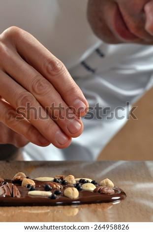 Cook preparing nuts dark chocolate bar.Adding nuts fruits on dark chocolate bar. - stock photo