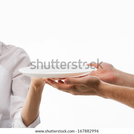 Cook's hand giving empty plate to man's hands on white background - stock photo