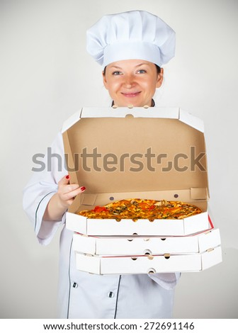 cook with a pizza in box on a light background - stock photo