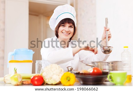 cook with ladle adds  spices into soup pan at kitchen - stock photo
