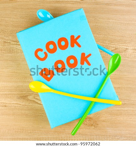 Cookbook and kitchenware on wooden background - stock photo