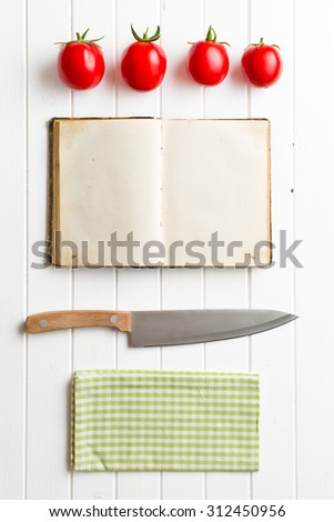cookbook and tomatoes on kitchen table - stock photo