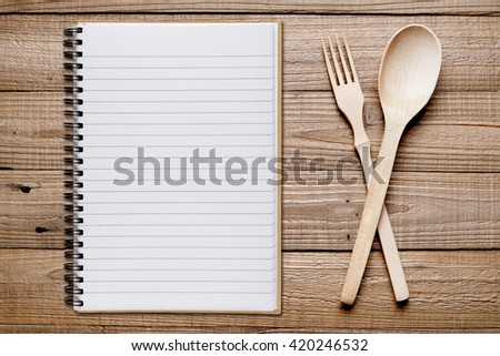 Cookbook, fork and spoon on wooden table top view - stock photo
