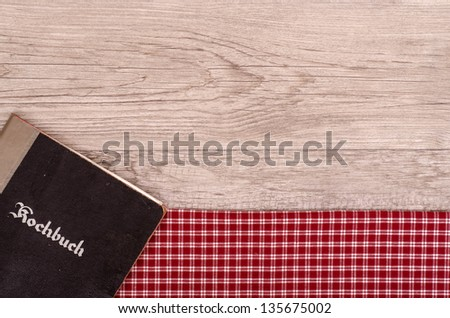 Cookbook on checkered table cloth and old wood - stock photo