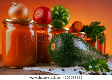 Cooked and mashed spicy squash puree (squash caviar) in glass jars on the table with fresh vegetables as ingredients - stock photo
