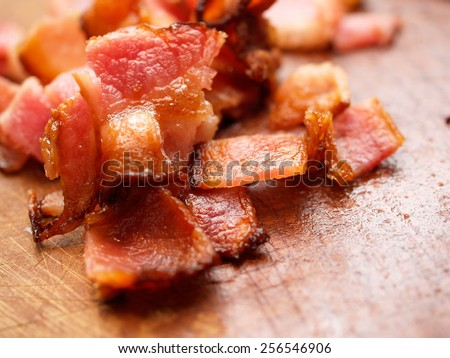 Cooked bacon pieces on wood. - stock photo